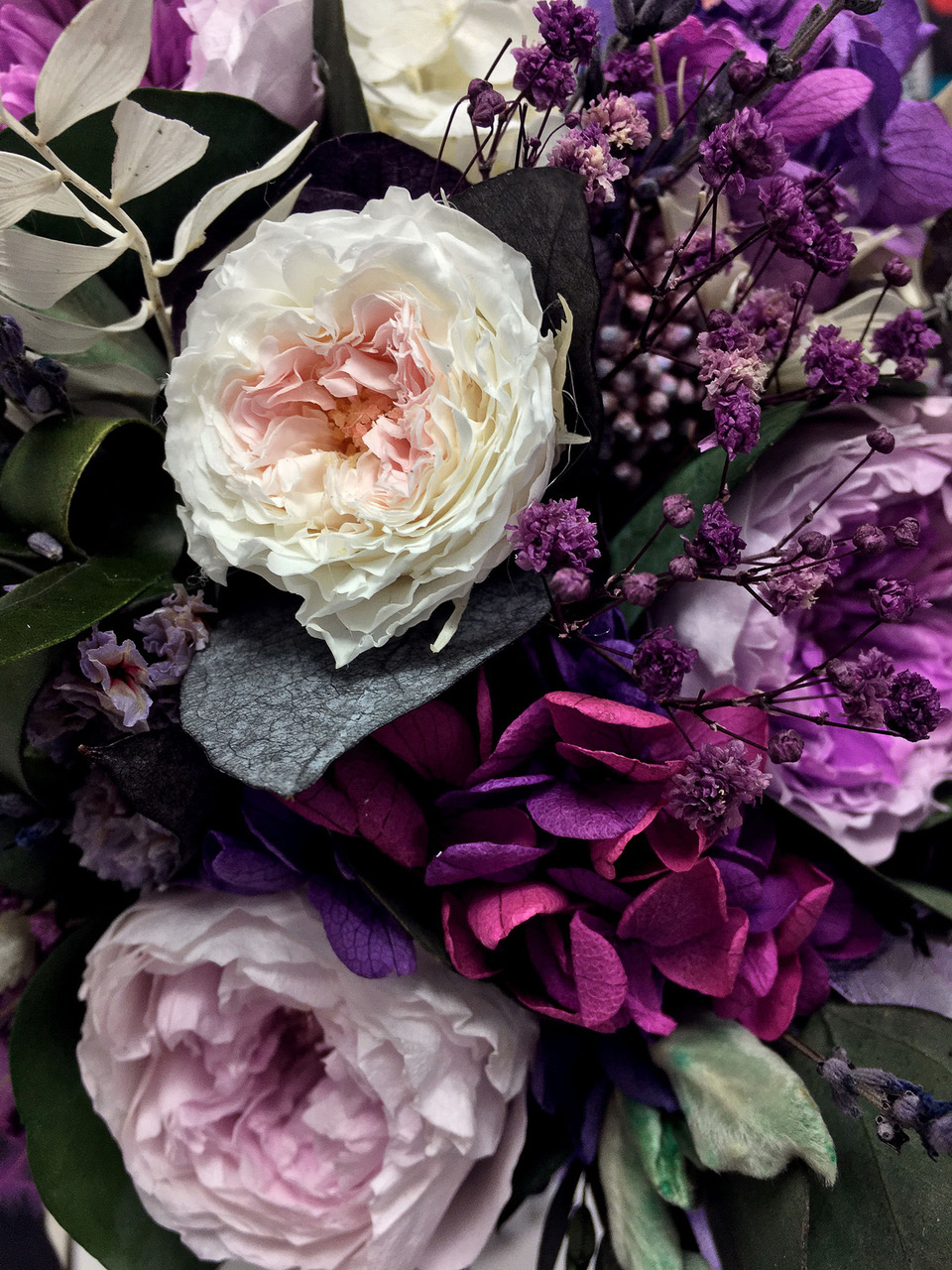 Beautiful bouquet of preserved flowers hydrangea, eucalyptus, purple and white peony roses. Dried flowers. Bouquet of spring flowers.