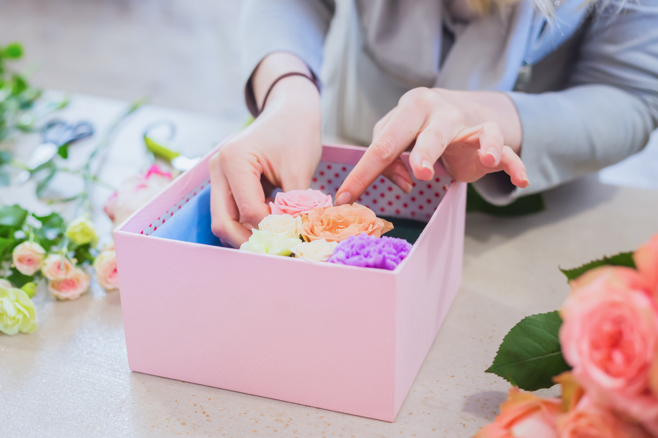 Woman floral artist, florist making gift box with flowers on table - close up